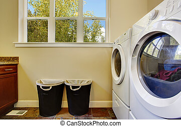 Bright ivory laundry room with white modern appliances and...