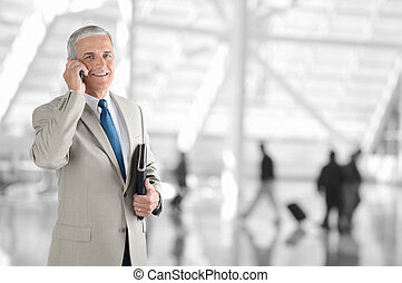 Businessman On Phone in Airport - A mature businessman on...