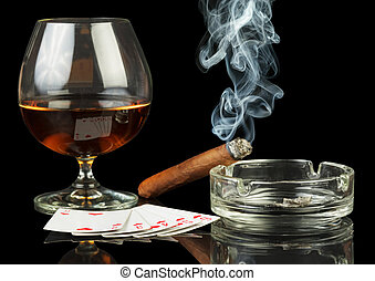 Cards, cigar and glass of whisky on glossy surface