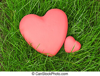 Red hearts on green grass - The red hearts lying on green...