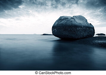 Beach and rocks - a wave rushes up a secluded beach around...