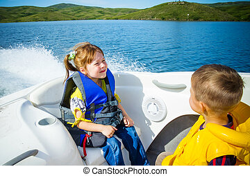 Travel of children on water in the boat - Two kids sitting...