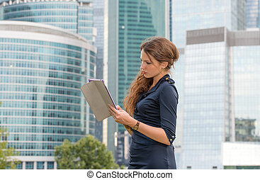 Beautiful girl in dress with tablet pc looks away near...