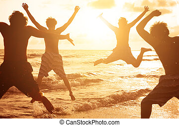 group of young people jumping at the beach with sunset...