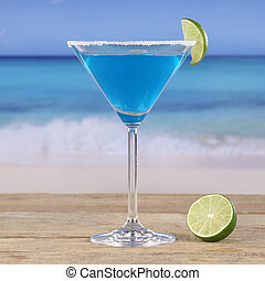 Blue Curacao cocktail drink on the beach and sea