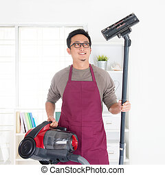 Asian man vacuuming - Asian man holding vacuum. House...