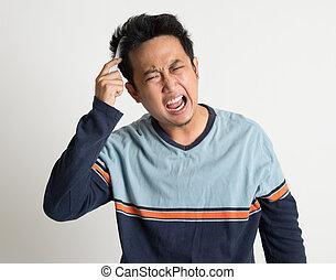 Asian man combing his tangled hair