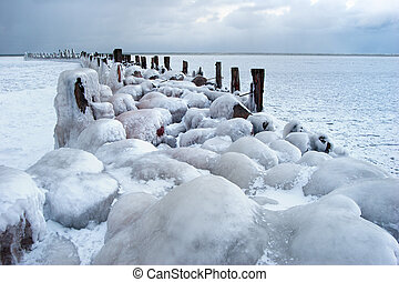 Frozen old pier with stones