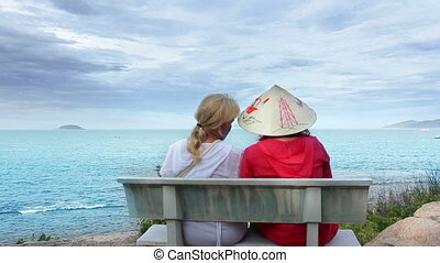 Two women sitting on a bench talking at the sea
