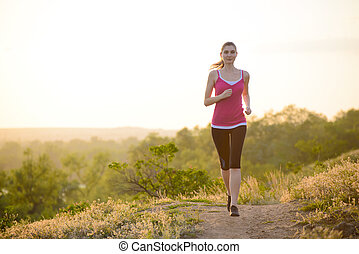 Young Beautiful Woman Running on Mountain Trail in the Morning