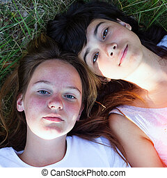 Two young girl lying on grass having good time.