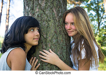 Two teen-girl playing on grass in the park.