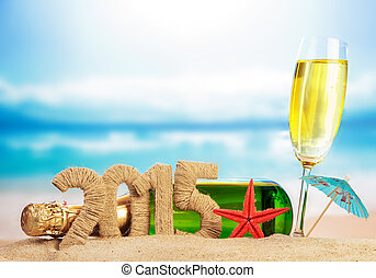 Champagne and New year sign on sandy beach