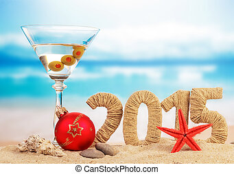 Cocktail, Christmas ball and New year sign on sandy beach