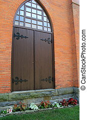 Brown arched doors in brick home