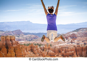 Young woman joyfully jumping in Bryce Canyon Park - Young...