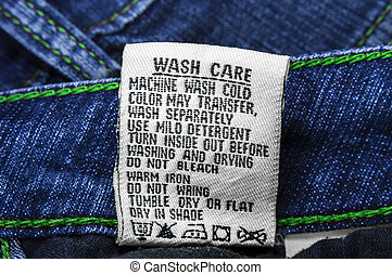 Wash care instructions on jeans of blue and green thread