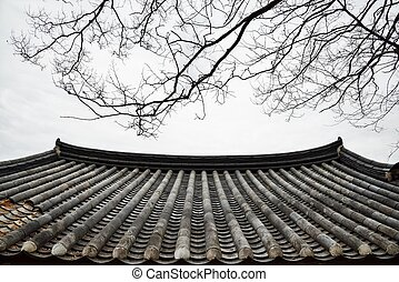 detail of Korean traditional tiled roof and branches