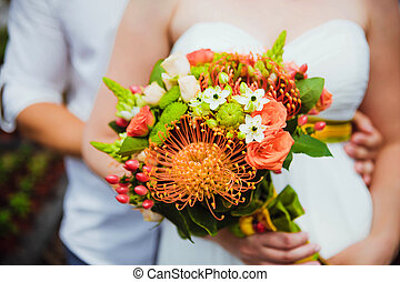 Wedding bouquet held by bride and groom Shallow depth of...