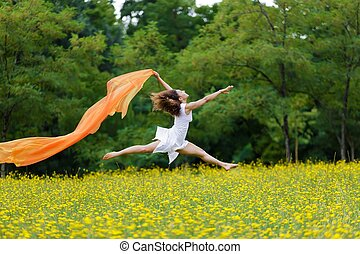 Agile woman leaping in the air trailing a scarf - Agile...