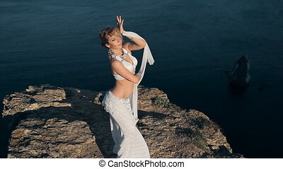 Girl masterly performs belly dancing beside an incredibly beautiful sea on a rock in Crimea
