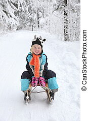 Sledding at winter timeSmiling girl on sleigh