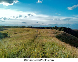 Man walking down country road in field, Belgorod Oblast....
