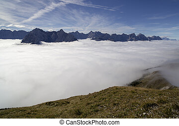 mountain peaks - many mountain peaks in the sun with clouds