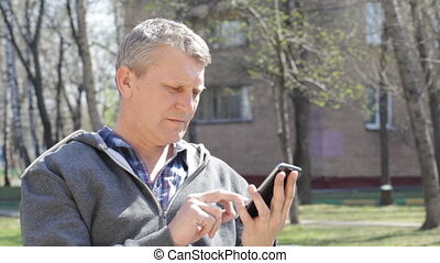 Mature man with the smartphone on the street