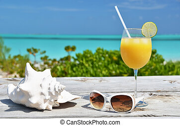 Orange juice and sunglasses on the beach Exuma, Bahamas