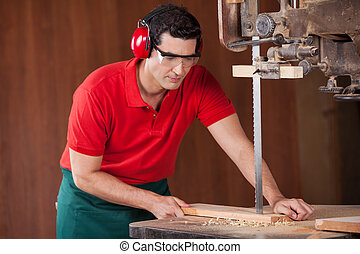 Carpenter Cutting Plank With Bandsaw - Young male carpenter...