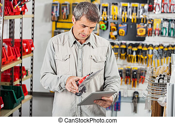 Man Scanning Product Through Digital Tablet - Mature man...