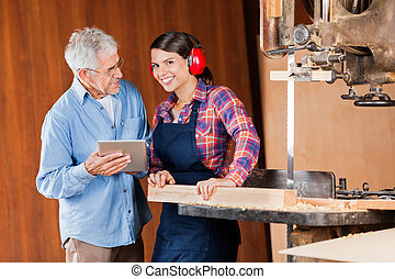 Carpenter With Senior Colleague Using Digital Tablet -...