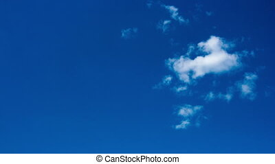 Small white cloud in the blue sky, timelapse