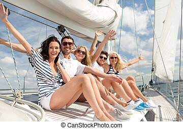 smiling friends sitting on yacht deck and greeting -...