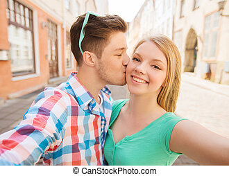 smiling couple with smartphone in city