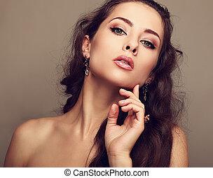 Sexy woman in fashion earrings touching clean face. Closeup