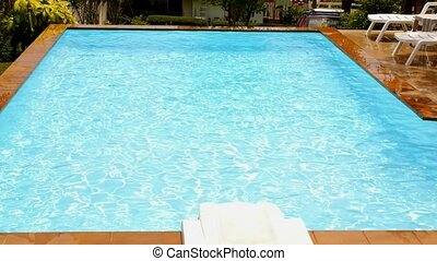 Blue Swimming Pool and Sun Loungers. Slow Motion.
