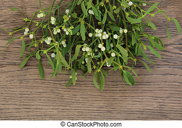 Mistletoe - Christmas mistletoe plant with berries over oak...