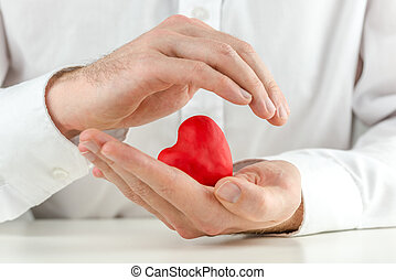 Caring man cupping a red heart in his hands with one hand...