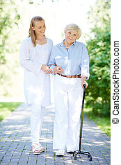 Walking with patient - Pretty nurse and senior patient with...