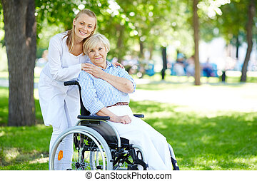 Taking care of patient - Pretty nurse and senior patient in...