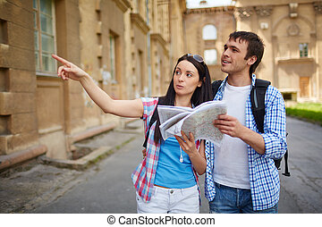 Tourists on journey - Couple of travelers with map...