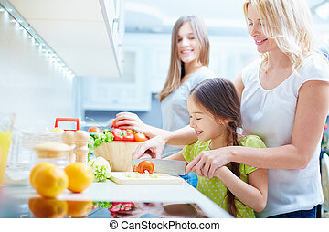 Cooking salad - Portrait of happy mother and two daughters...