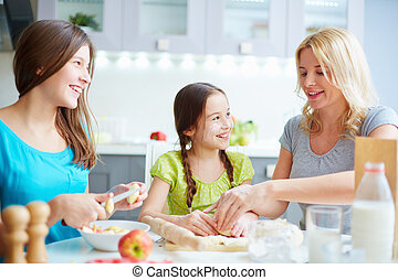 Enjoying cooking - Portrait of happy girls helping their...