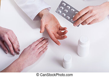 Doctor giving patient medicines closeup isolated hands photo