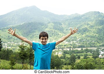 boy and mountains - boy raised his hands to the sun on a...
