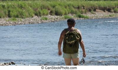 Fisherman goes along the riverbank