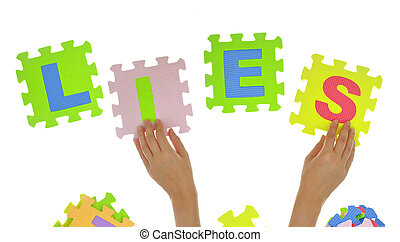 """Hands forming word """"Lies"""" with jigsaw puzzle pieces"""