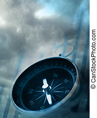 Compass on dark cloudy sky background